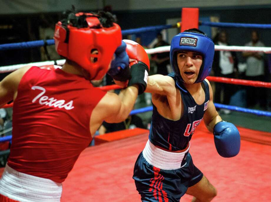 "Gilbert Renteria, right, fighting Lazaro Ramirez in a 114-pound bout at the Houston Golden Gloves tournament last weekend, believes boxing kept him from being ""a rebel. A bad one."" Photo: Brett Coomer, Staff / © 2015 Houston Chronicle"