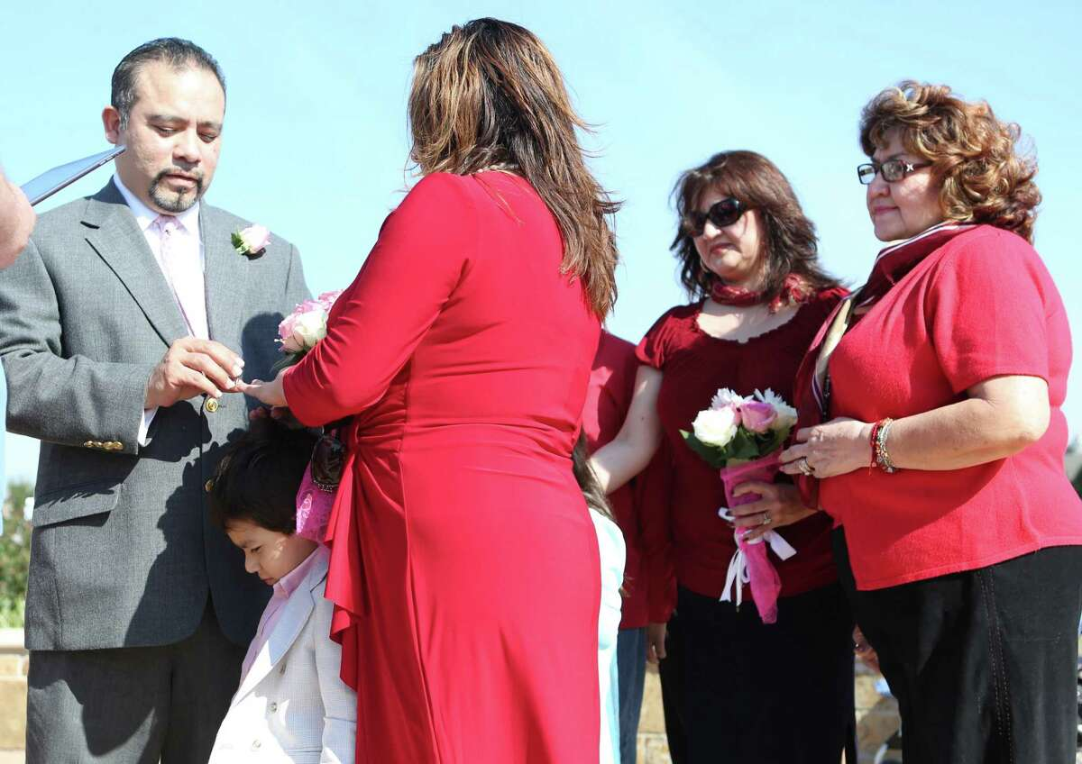 Joe and Sylvia Rodriguez get married while son Joseph, 5, stands between them during a Valentine's Day wedding ceremony at Current, a Christian Church, on Saturday, Feb. 14, 2015, in Houston.