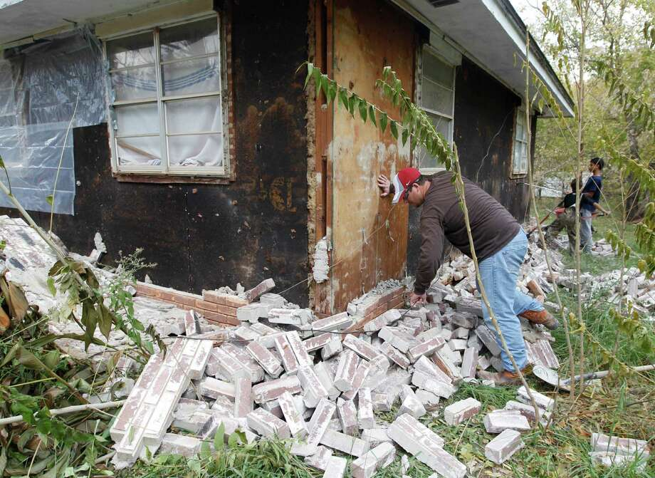 Chad Devereaux examines bricks that fell from three sides of his in-laws' home in Sparks, Okla., after two earthquakes hit the area in less than 24 hours in 2011. Federal research says small quakes could lead to much larger ones. Photo: Sue Ogrocki, STF / AP