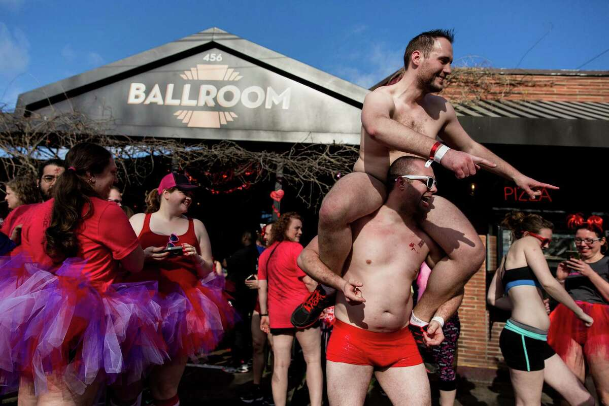 Men piggyback outside of the annual Cupid's Undie Run Saturday, February 14, 2015, in Seattle's Fremont neighborhood. Hundreds of people gathered at the Ballroom and then completed a roughly mile-long run in their skivvies. The event was a fundraiser for The Children's Tumor Foundation.