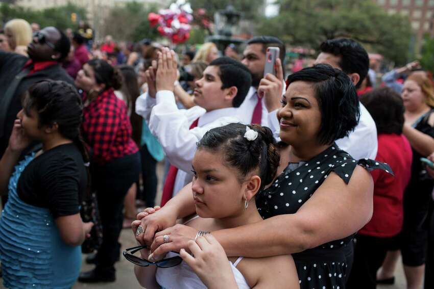 Toni Chararria stands with her arms around her daughter Madison Chararria, 11, as they watch Toni's father in law get married during one of the free mass wedding ceremonies held annually on the steps of the Bexar County Courthouse on Valentine's Day, Saturday, February 14, 2015.