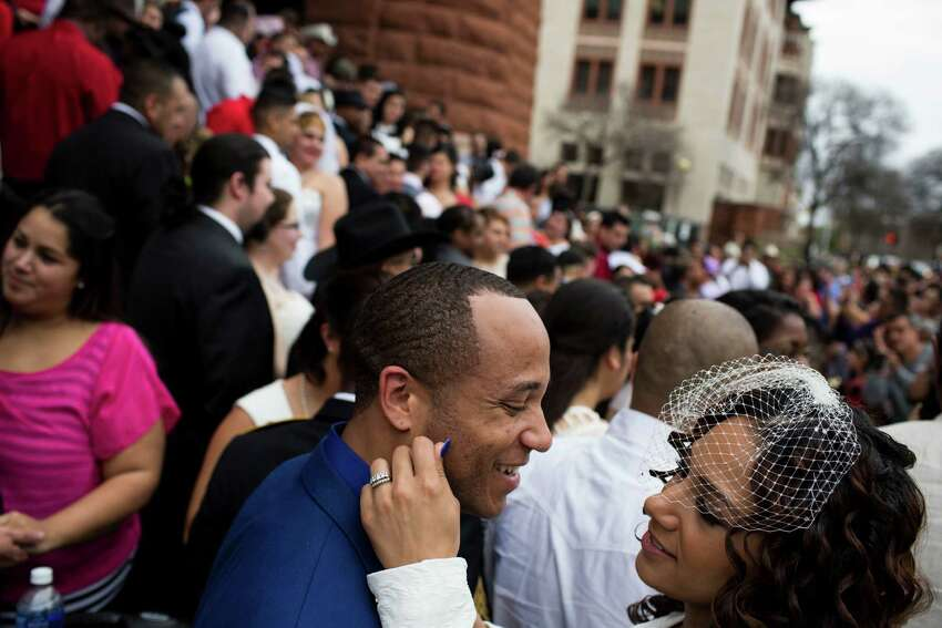 Jessica Freeman puts her hand on Quincy Freeman during one of the free mass wedding ceremonies held annually on the steps of the Bexar County Courthouse on Valentine's Day, Saturday, February 14, 2015.