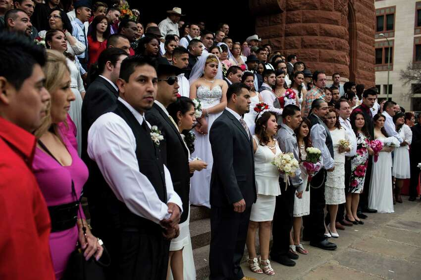Dozens of couples wait to be wed during one of the free mass wedding ceremonies held annually on the steps of the Bexar County Courthouse on Valentine's Day, Saturday, February 14, 2015.