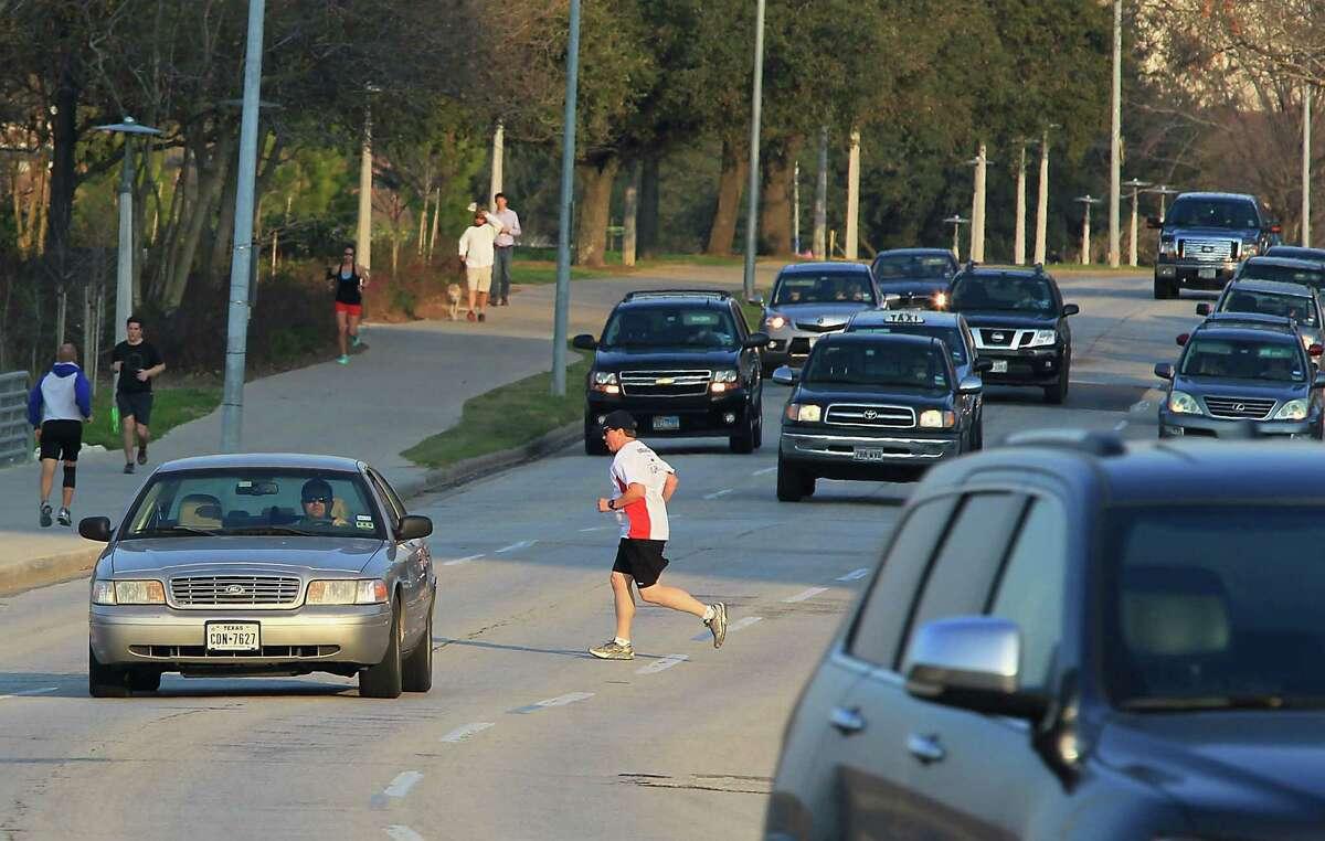 Pat Dunnahoo, center, jogs across Allen Parkway near Taft on Feb. 12, 2015, in Houston.