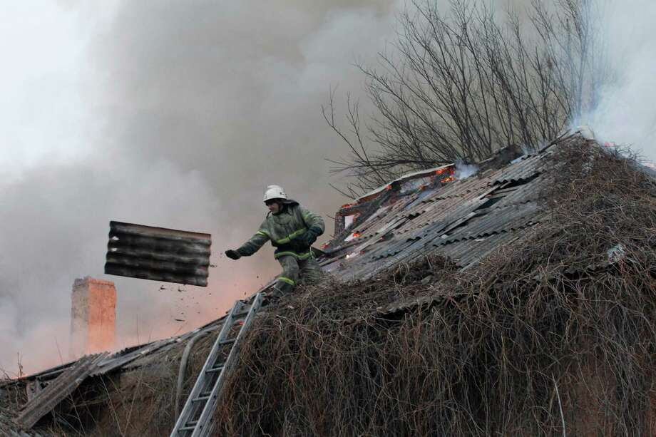 A firefighter dismantles a roof  to extinguish a building on fire after shelling between Russian-backed separatists and Ukrainian government in residential area of the town of  Artemivsk, Ukraine, Saturday, Feb. 14, 2015. Despite a looming cease-fire deal for eastern Ukraine, a government-held town 40 kilometers (25 miles) behind the front line has been hit by shelling. The deadline for the warring sides to halt hostilities is Sunday morning at one minute after midnight. (AP Photo/Petr David Josek) Photo: Petr David Josek, STF / AP