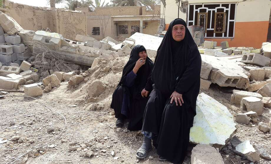 Iraqi women weep over their destroyed home after returning Saturday to the village of Al-Mansuriya, north of Baghdad. They and thousands of others were displaced because of fighting between government forces and militants from the Islamic State. Iraqi forces and allied militia retook Al-Mansuriya two weeks ago. Photo: YOUNIS AL-BAYATI, Stringer / AFP