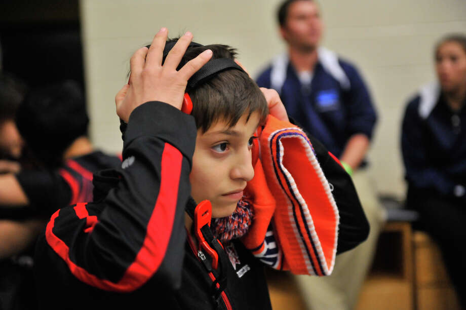 Wagner's Julie Mata (adjusts her headgear before her110lb class  Region IV-6A Wrestling tournament at Littleton Gym Saturday against King's Lexie Escamilla. Photo: Robin Jerstad / San Antonio Express-News