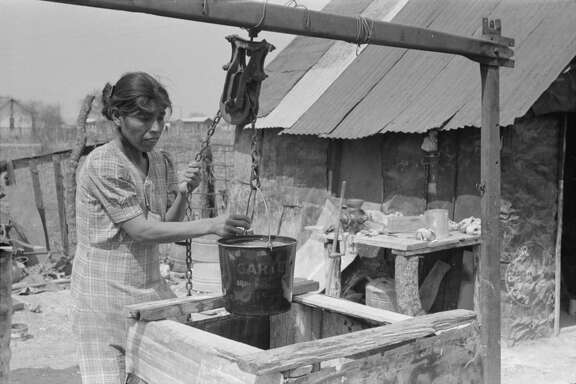 """Mexican woman drawing a bucket of water from backyard well, San Antonio"" is the label on this March 1939 photo by Russell Lee. Unsanitary living conditions in the 1800s and even into the 1900s made it easy for diseases to spread. Farm Security Administration - Office of War Information Photograph Collection."