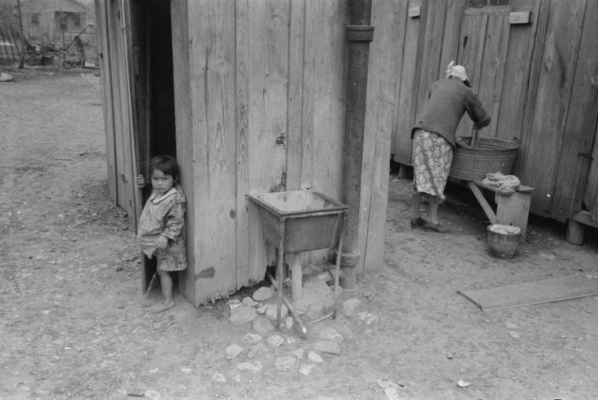 """This photo labeled """"Mexican girl coming from privy, woman washing clothes, San Antonio"""" in March 1939 by Russell Lee shows poor living conditions in the 30s in San Antonio. Farm Security Administration - Office of War Information Photograph Collection."""