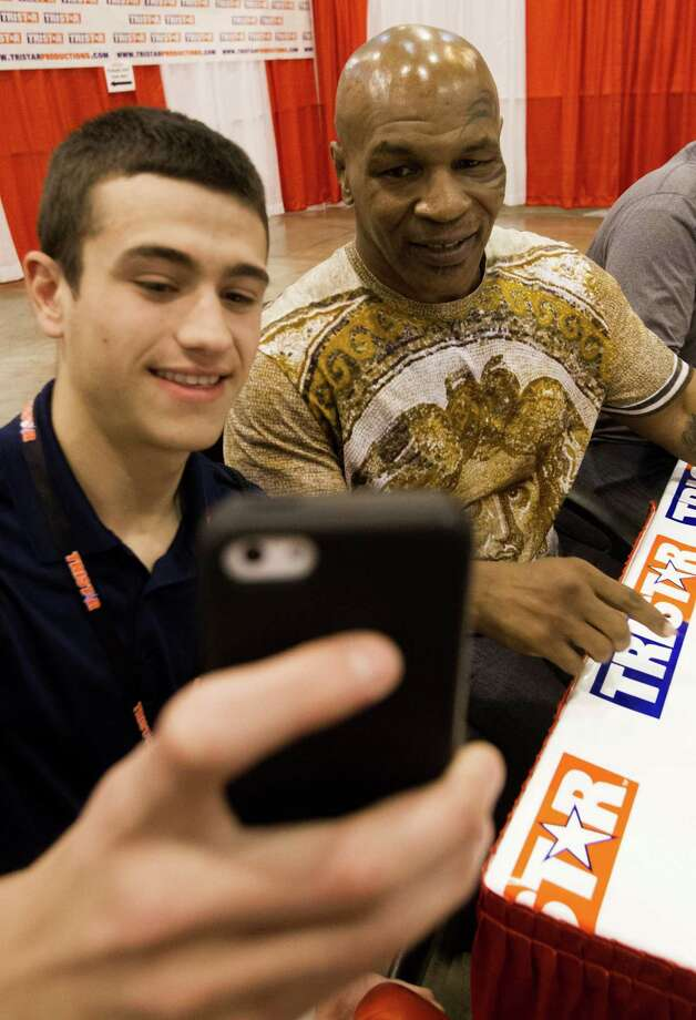 It's not every day you can take a selfie with former heavyweight boxing champion Mike Tyson, but Clay Hatcher got one Saturday at Tristar's 29th annual Houston Collectors Show at NRG Center. The show continues from 10 a.m. to 4 p.m. today. Photo: J. Patric Schneider, Freelance / © 2015 Houston Chronicle