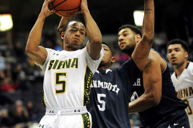 Siena's Evan Hymes, left, looks to pass as Monmouth's Deon Jones defends during their basketball game on Saturday, Feb. 14, 2015, at Times Union Center in Albany, N.Y. (Cindy Schultz / Times Union) Photo: Cindy Schultz / 00030520A