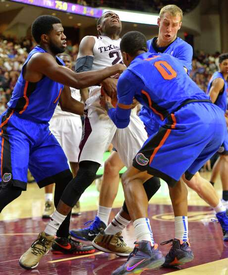 Texas A&M's Danuel House, center, wrestles for control of the ball with Florida's Eli Carter, left, Kasey Hill (0) and Alex Murphy during the first half of an NCAA basketball game, Saturday, Feb. 14, 2015, in College Station, Texas. Texas A&M won the game 63-62. (AP Photo/College Station Eagle, Sam Craft) Photo: Sam Craft, Associated Press / College Station Eagle