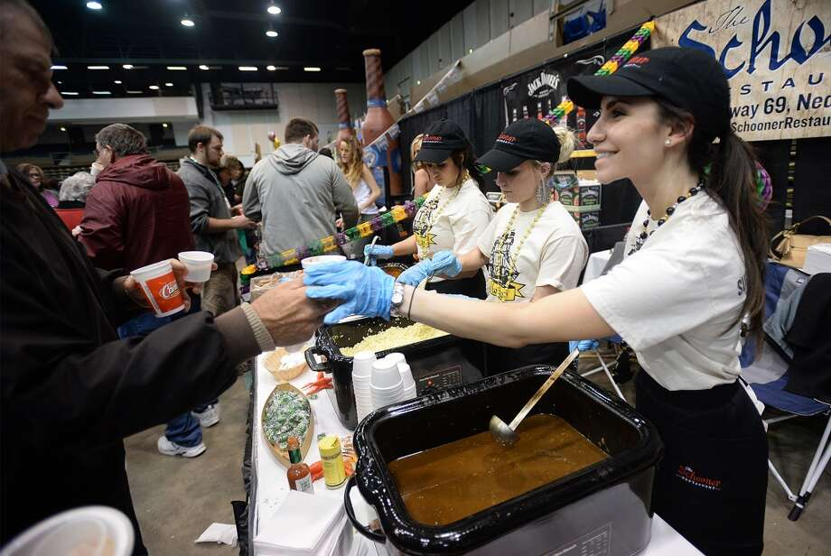 Maria Megas hands off a cup of the Schooner's gumbo to a Taste of the Triangle patron Tuesday night at the Beaumont Civic Center. Dozens of local venders provided guests with samples their foods, drinks and services.   Photo taken Tuesday, March 04, 2014 Guiseppe Barranco/@spotnewsshooter