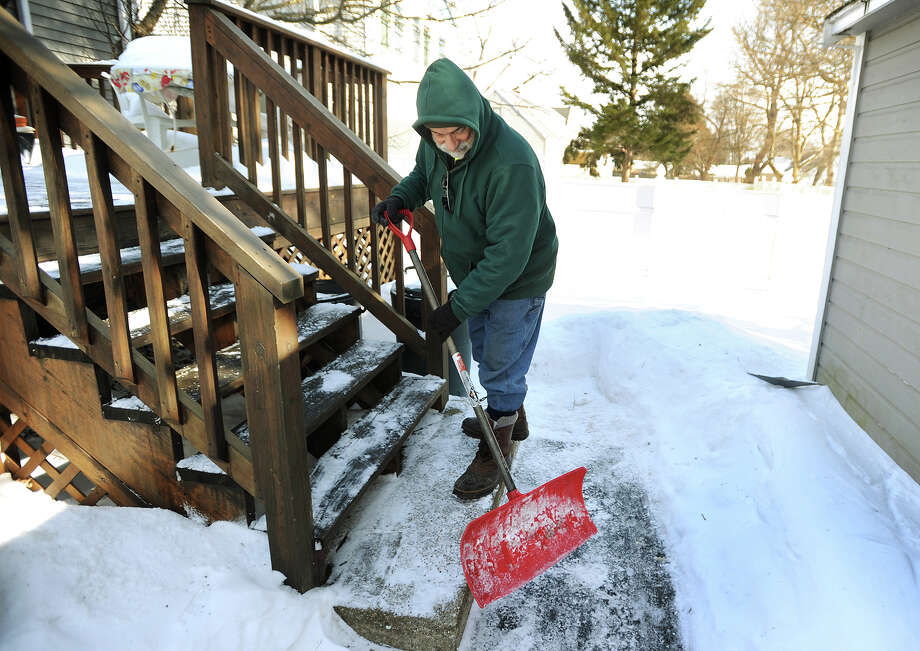 Following Saturday's snow, Jim Faris of Oronoque Home Improvement shovels snow from the steps and walkway of a home on Greenlawn Avenue in Stratford, Conn. on Sunday, February 15, 2015. Faris said he clears snow first at homes of the handicapped and elderly. Photo: Brian A. Pounds / Connecticut Post