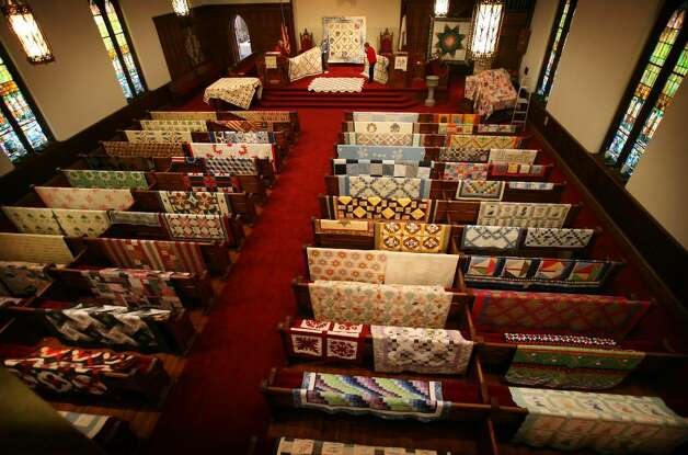 "Organizers put the finishing touches on the display for the annual quilt show at the Southport Congregational Church in Fairfield on Wednesday, March 3, 2010. The show runs Friday and Saturday, with 165 quilts being displayed as well as this year's special exhibit, ""The World of Miniatures"". Photo: Brian A. Pounds / Connecticut Post"