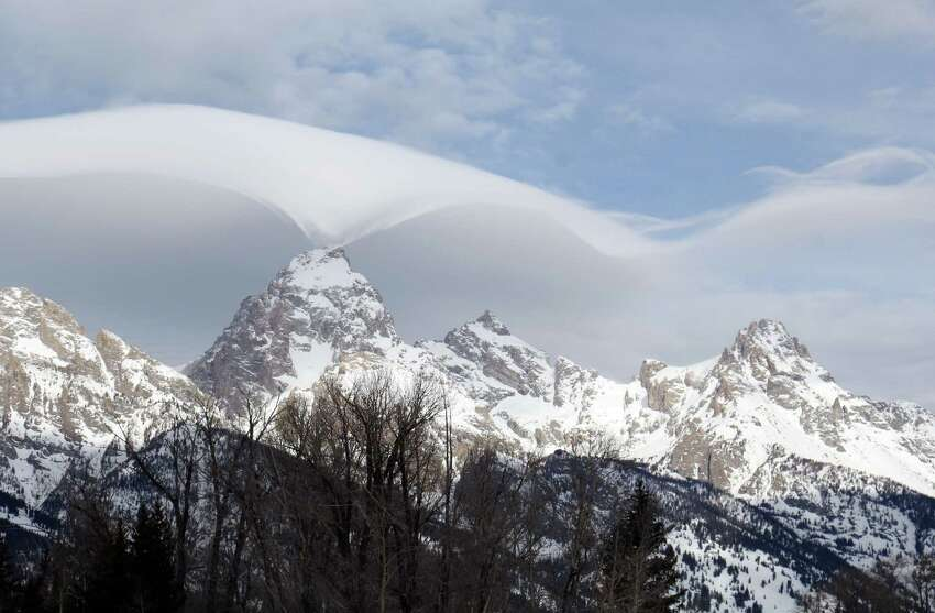 This photo taken Thursday, Feb. 12, 2015, and provided by the Grand Teton National Park, shows an unusual cloud formation across the summit of the Grand Teton in this view from the park's headquarters campus at Moose, Wyo.