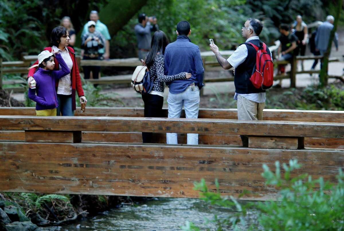 With Redwood Creek running, Muir Woods visitors stopped for pictures on a bridge Sunday February 15, 2015. Admission is free this holiday weekend at all national parks including Muir Woods in Marin County. Parking, as usual, was the biggest problem for visitors to the woods.