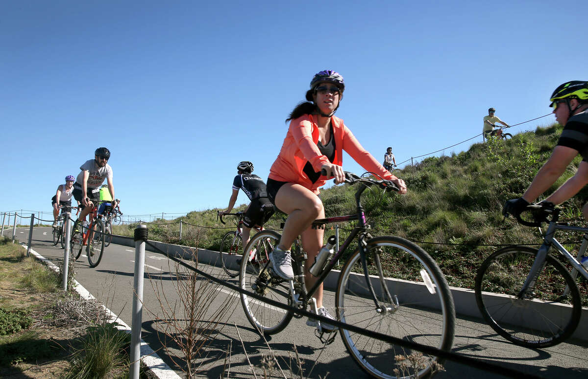 Bicyclists ride near the Golden Gate Bridge. A bill has been introduced in the state Senate to make helmets mandatory for all bicycle riders, requiring adults to wear them, not just minors.