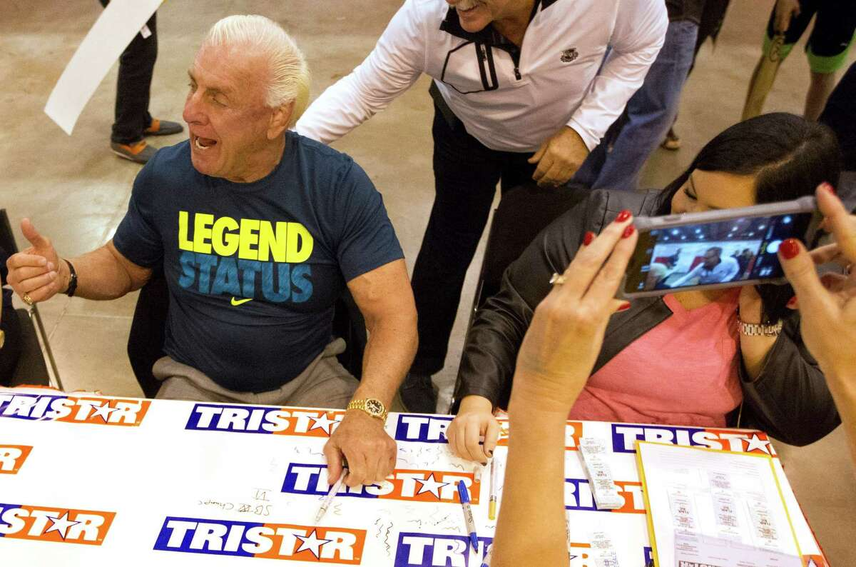 WWE wrestler Ric Flair signs autographs for fans during the Tristar autograph show at NRG park on Sunday, Feb. 15, 2015, in Houston.