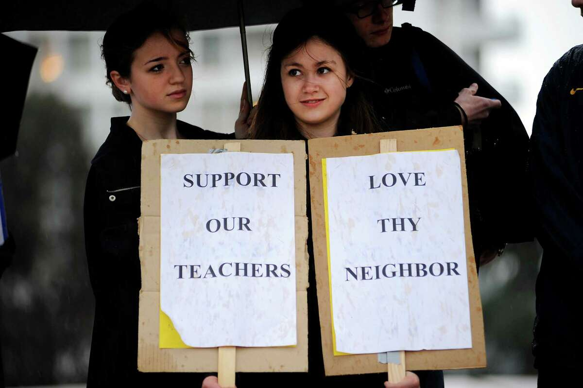 Sacred Heart Cathedral Preparatory student Julie Cravotto holds signs as she stands with other students from local Catholic high schools gathered to protest Archbishop Cordileone at St. Mary's Cathedral in San Francisco.