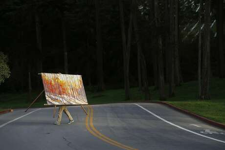At the end of a long day, Nicholas Coley carries his nearly complete painting to his truck in the Presidio on Wednesday Feb. 11, 2015 in San Francisco, Calif.