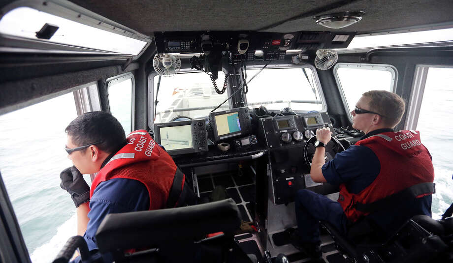 United States Coast Guard Chief Petty Officer Benjamin Gamad (left) and Petty Officer 2nd Class Jacob Lovell look for illegal fishing lines, Monday Dec. 29, 2014, in the Gulf of Mexico off South Padre Island. Photo: Edward A. Ornelas, San Antonio Express-News / © 2014 San Antonio Express-News