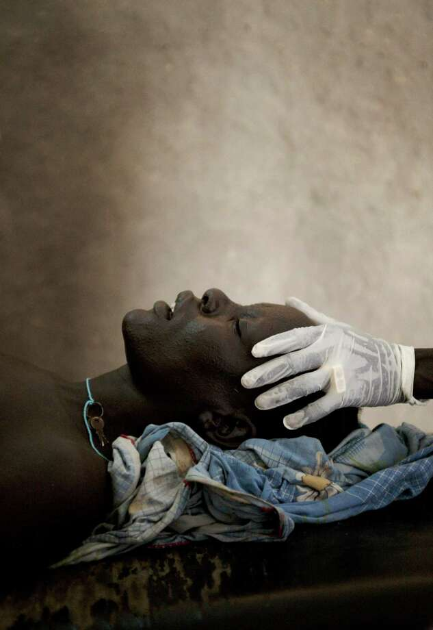 Southern Sudan, 2009 - A Nuer woman giving birth to her still-born baby. Photo: Giles Duley / Special To The Chronicle / ONLINE_CHECK
