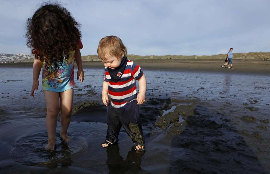 Dunya Ozak (left), 3, and Everest Hunt, 1, splash in puddles on the shore of Ocean Beach in San Francisco, Calif., Sunday, February 15, 2015, during a rare heat wave that hit the Bay Area.The hottest temperatures of the year so far will cook the Bay Area on Monday with the mercury spiking into the triple digits in some areas, forecasters said. Photo: Jessica Christian, The Chronicle