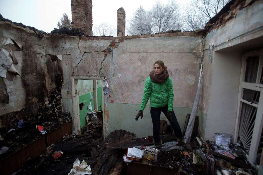 A member of the medical staff salvages items from the rubble of a destroyed clinic where she'd had worked in the eastern Ukraine village of Opytne. Photo: Petro Zadorozhnyy /Getty Images / AFP