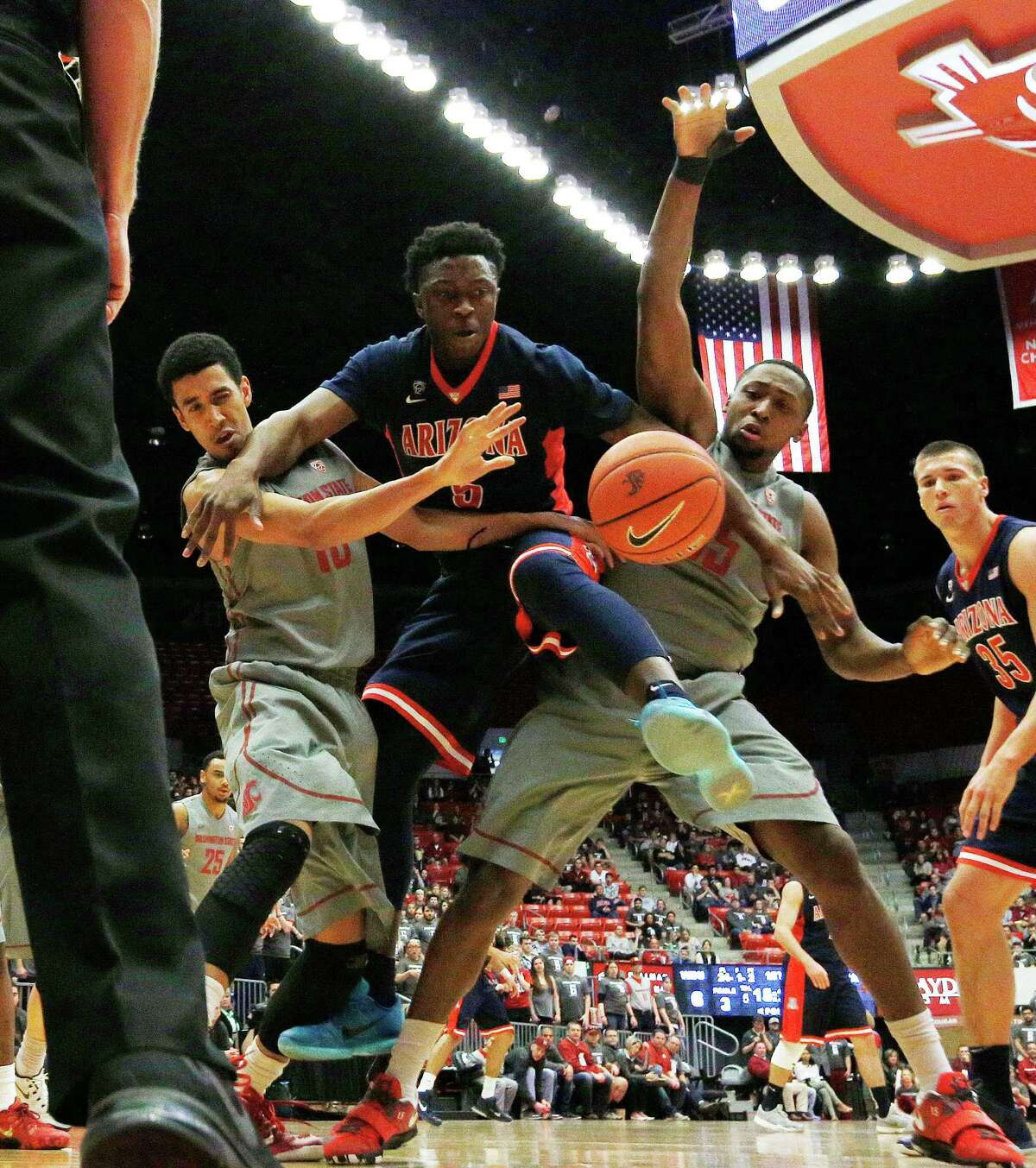Arizona's Stanley Johnson, center, fights for a rebound against Washington State's Dexter Kernich-Drew, left, and Junior Longrus during the first half of an NCAA college basketball game, Sunday, Feb. 15, 2015, in Pullman, Wash. (AP Photo/Young Kwak) ORG XMIT: WAYK106