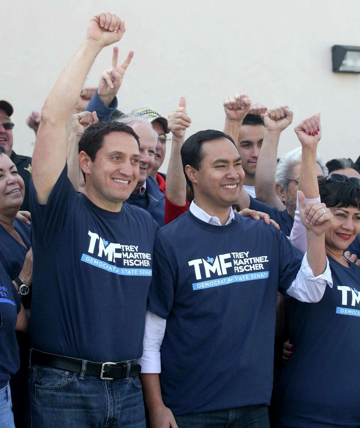 In campaign gear, Trey Martinez Fischer rallies supporters, including U.S. Rep. Joaquin Castro, at the law office of state Rep. Roland Gutierrez.