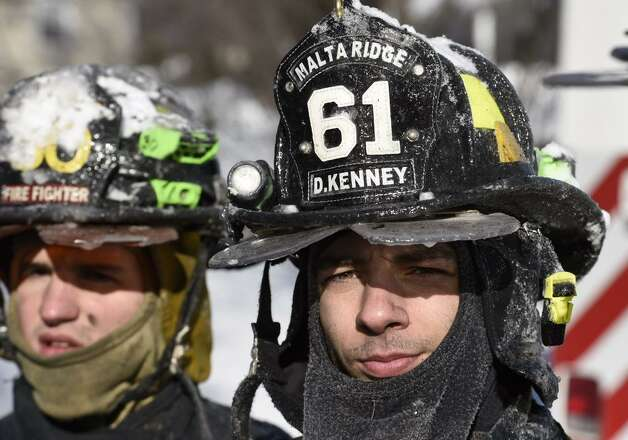 Firefighter Devin Kenney, right, of the Malta Ridge Fire Department is covered with ice after fighting a fire Monday at a home at 12 North Ridge in Malta. (Skip Dickstein / Times Union)