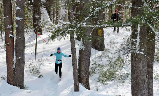 Women's first-place finisher Karen Howe of Rochester, a member of the Medved Snowshoe Team, makes her way down a hill  during the 12th Annual Camp Saratoga 8k Snowshoe Race on Sunday, Feb. 15, 2015, in Wilton, N.Y.  The race is a U.S. National Snowshoe Championships qualifier.  Twelve team members came in for the race.   (Paul Buckowski / Times Union) Photo: Paul Buckowski / 00030550A
