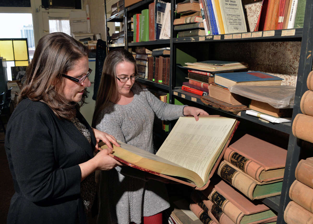 Executive director Susan Holland, left, and director of preservation services Cara Macir consult county indexes in Historic Albany Foundation's resource center.