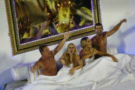 Performers from the Mocidade samba school greet spectators from their float during the Carnival parade at the Sambadrome in Rio de Janeiro, Brazil, Monday, Feb. 16, 2015.