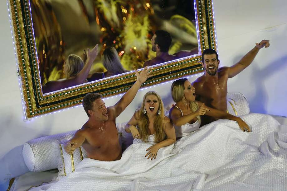 MEANWHILE, ON THE FULL-SWAP FLOAT ...Performers from the Mocidade samba school wave to spectators from under the sheets during the carnival parade at the Sambadrome in Rio de Janeiro. Photo: Felipe Dana, Associated Press