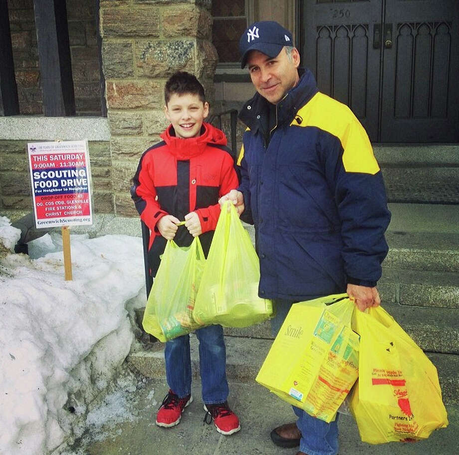 "Helping out at last yearís ""Scouting for Food"" drive are Pack 10 Cub Scout Daulton Kendall and CT State Representative and food drive honorary chair Fred Camillo. Greenwich residents are urged to gather food items and donate on March 7 to benefit Neighbor to Neighbor. Photo: Contributed Photo / Greenwich Time Contributed"