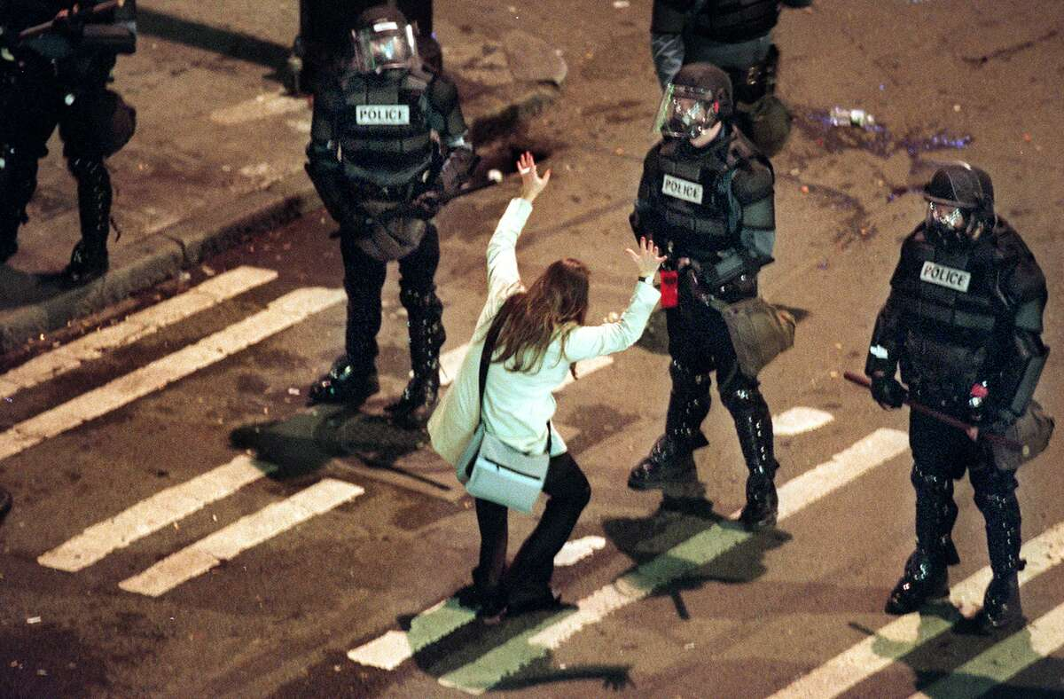 A woman taunts police to shoot her on Yesler street in Seattle during a protest after the Marti Gras celebration when police were clearing the streets early the morning of Feb. 25, 2001.