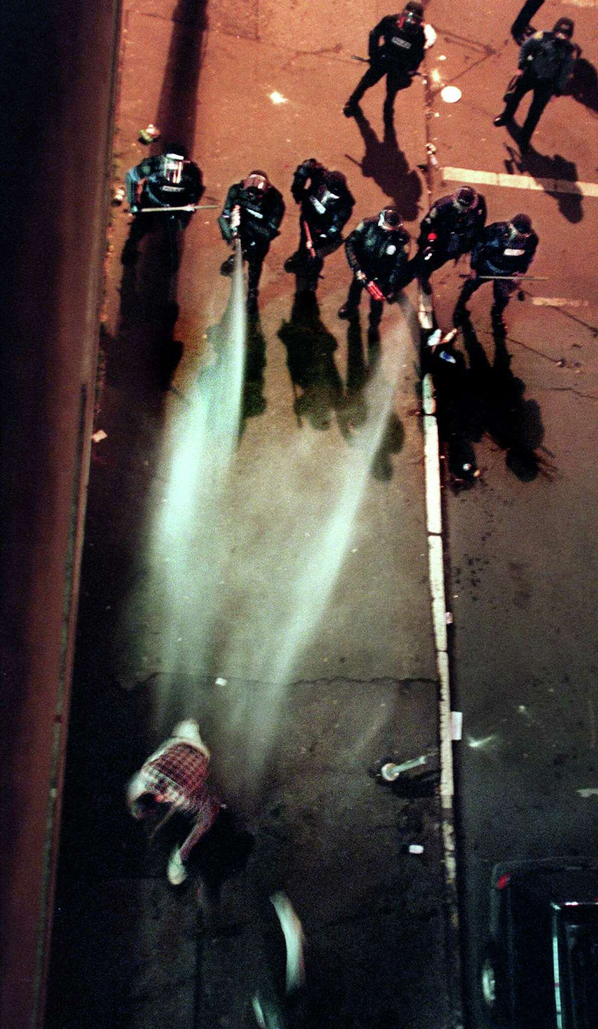 Seattle Police officers gas a man on James street in Seattle while clearing the streets after a Mardi Gras celebration which turned into a protest in Pioneer Square early the morning of Feb. 25, 2001.
