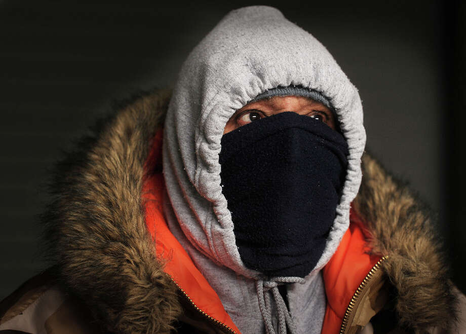 Dewell Santos, of Bridgeport, covers everything but his eyes in an effort to stay warm after riding his bicycle to work on State Street in Bridgeport, Conn. on Monday, February 16, 2015. Photo: Brian A. Pounds / Connecticut Post