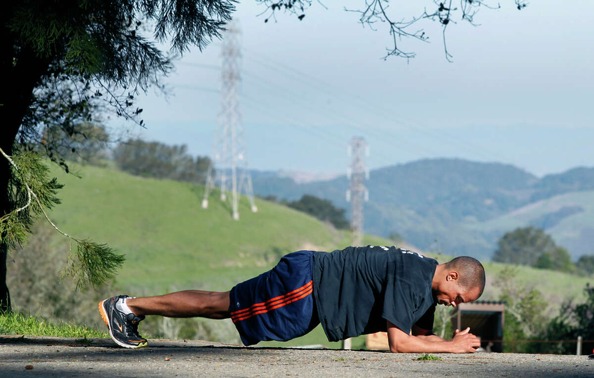 Seth Steward stretches after completing a 6-mile run on the Nimitz Way trail at Tilden Park in Berkeley, Calif. on Monday, Feb. 16, 2015. The Bay Area continues to bask in unseasonably warm weather while much of the country digs out from snowstorms.