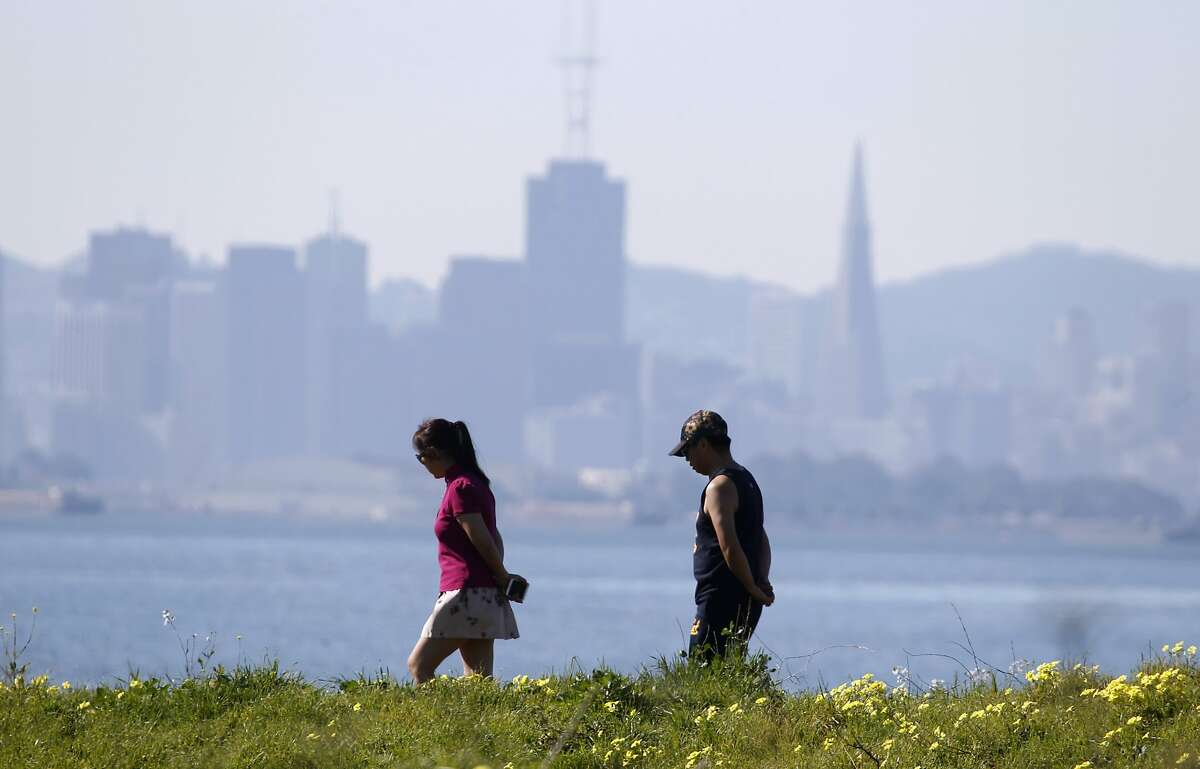 Hikers walk along the Berkeley Marina waterfront in Berkeley, Calif. on Monday, Feb. 16, 2015. The Bay Area continues to bask in unseasonably warm weather while much of the country digs out from snowstorms.