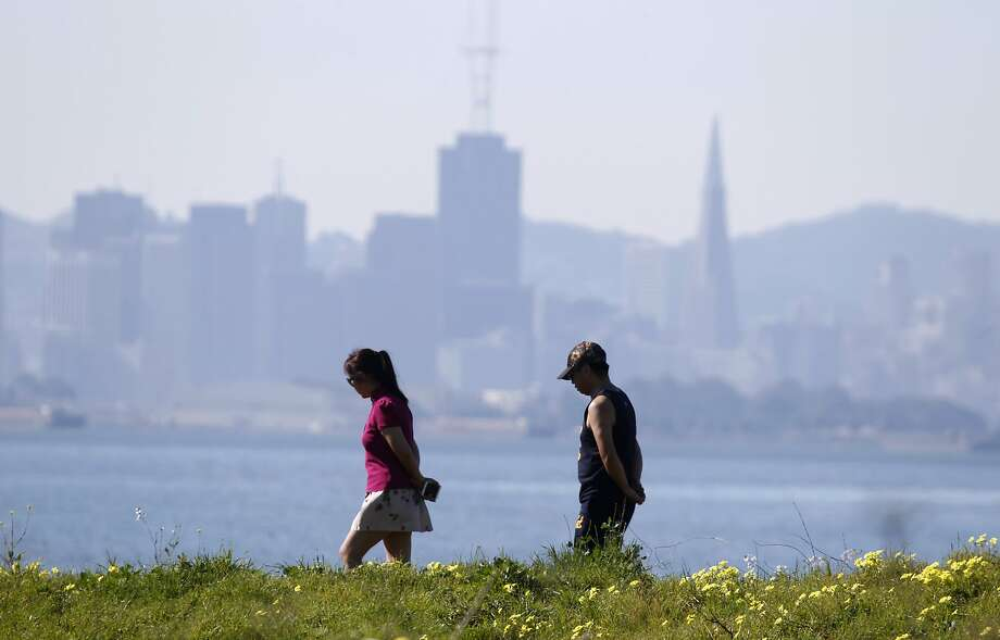 Hikers walk along the Berkeley Marina waterfront in Berkeley, Calif. on Monday, Feb. 16, 2015. The Bay Area continues to bask in unseasonably warm weather while much of the country digs out from snowstorms. Photo: Paul Chinn, The Chronicle