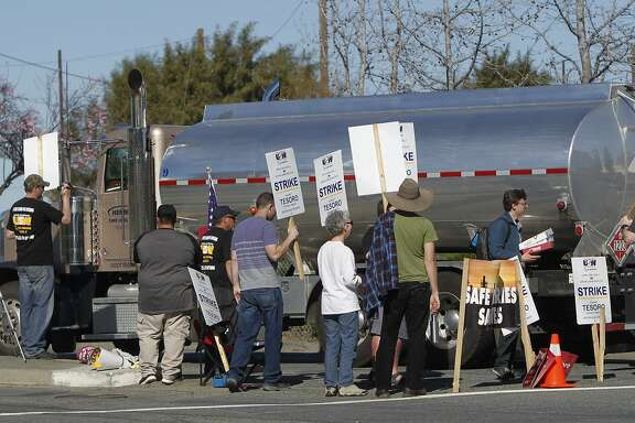 A group of United Steelworkers approach a truck crossing the picket line while protesting outside the Tesoro Golden Eagle Refinery in Martinez, Calif. Saturday, February 14, 2015.
