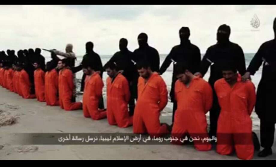 An image grab from a video posted Sunday on Youtube shows black-clad Islamic State militants in Libya with kidnapped Egyptian Coptic Christians on the Mediterranean coast of Libya. <137>according to the video. The Egyptian Orthodox Church confirmed late on Sunday the killing of 21 Egyptian Coptic Christians kidnapped by Islamic State (IS) militant group in Libya, state-run MENA news agency reported. (Xinhua/Sipa USA/TNS)<137> Photo: Xinhua /Tribune News Service / Sipa USA