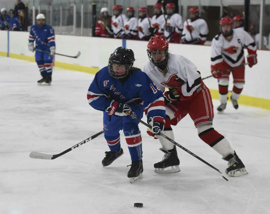 Fairfield's Mary Edmonds, left, skates around Greenwich's Claire Eschricht on her way to a goal in Fairfield's 7-4 win over Greenwich in the high school girls hockey game at the Dorothy Hamill Rink in Greenwich, Conn. Monday, Feb. 16, 2015. Photo: Tyler Sizemore / Greenwich Time