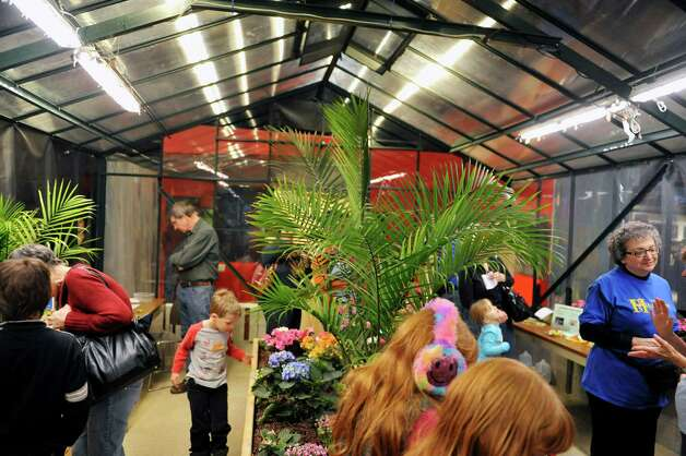 Visitors look over butterflies at the butterfly house inside the MiSci, the Museum of Innovation and Science on Monday, Feb. 16, 2015, in Schenectady, N.Y.  The butterfly house is open through April 19th.   (Paul Buckowski / Times Union) Photo: Paul Buckowski / 00030569A