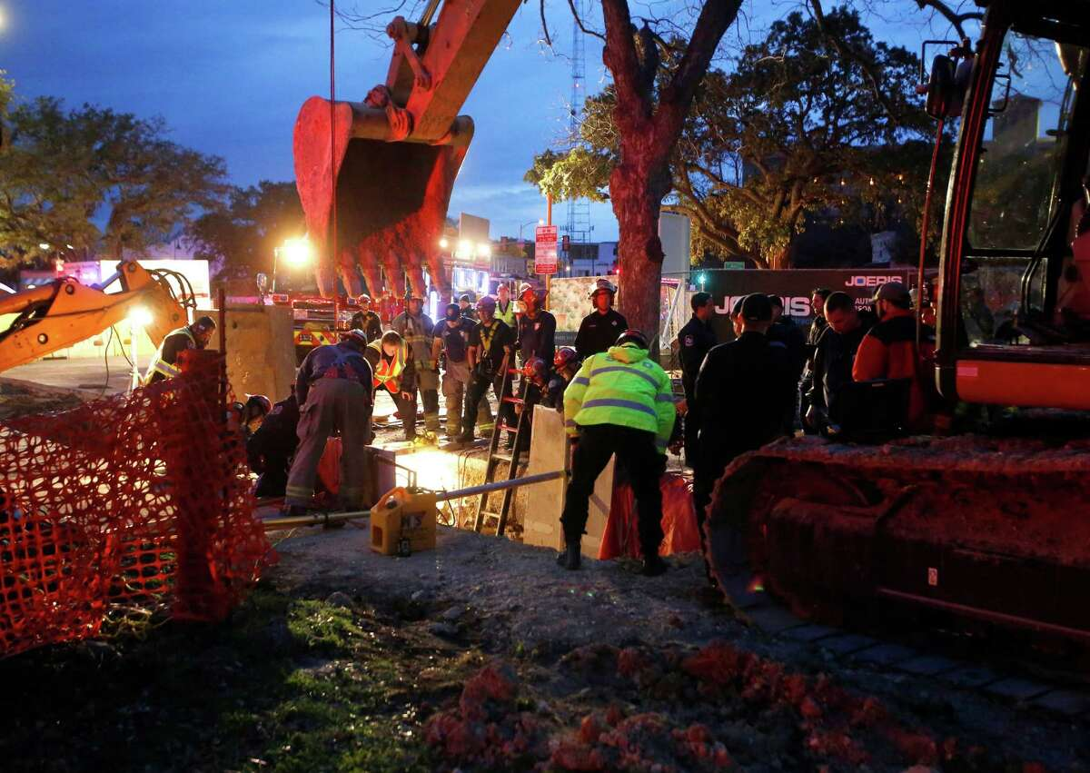 San Antonio Fire Department units look into a deep trench at a Southtown construction site Monday night. More than 20 rescue units rushed to the construction site Monday evening after a worker became trapped in the trench that was partially filled with cement near South Alamo Street and East Cesar Chavez Boulevard. The worker, 63, was alert, talking and breathing after being stuck in the cement about about thigh deep.