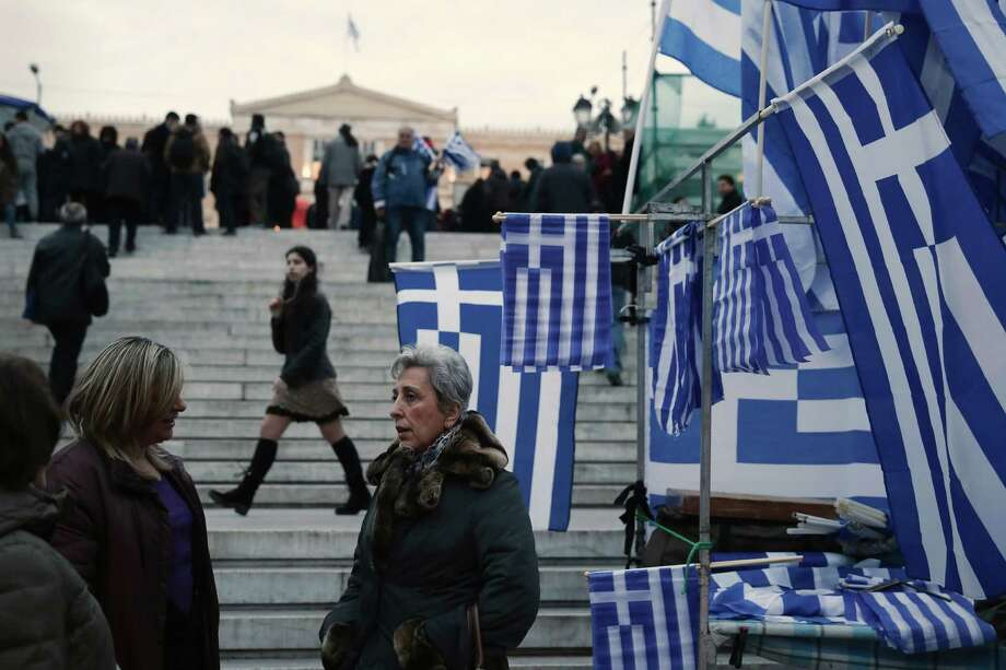 Greek flags were for sale Monday in Athens' Syntagma Square as Greece and its creditors in the 19-country eurozone struggled to bridge a large gap over  the country's request to ease its bailout terms. Photo: Petros Giannakouris, STF / AP