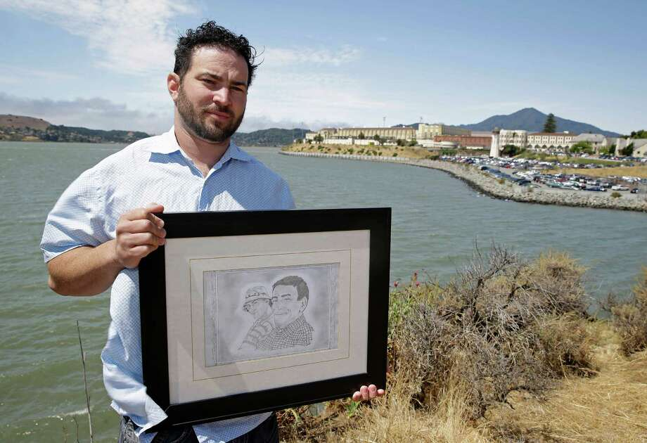 Dan Ager holds a graphite sketch showing his father, Alan Ager, and him, while standing outside San Quentin State Prison inCalifornia. Alan Ager, a convicted child molester, was killed by his cellmate in 2010 at Salinas Valley State Prison. Photo: Eric Risberg, STF / AP